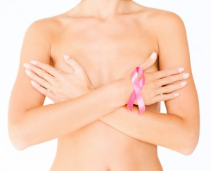 woman covering breasts holding breast cancer ribbon